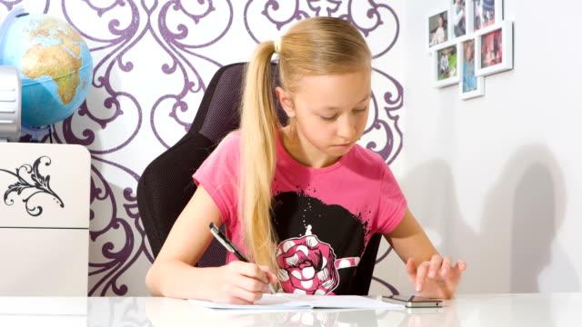 girl doing homework using smartphone calculator - çalışma kitabı stok videoları ve detay görüntü çekimi