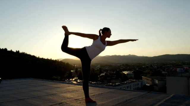 CLOSE UP: Girl doing lord of the dance yoga pose on top of skyscraper at sunrise