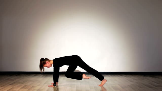 Girl doing low lunge yoga pose from downward facing dog position video