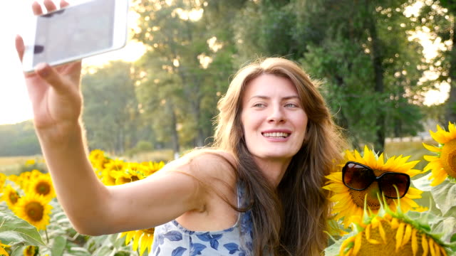 Girl doing selfie with sunflower. HD video