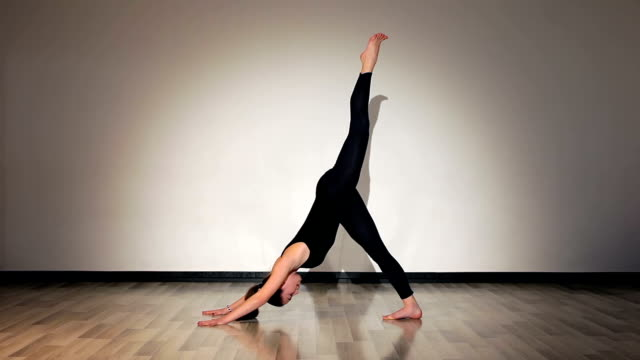 Girl doing yoga exercises downward facing dog leg lift video