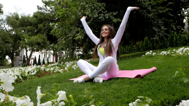 Girl doing yoga pose at the park in the morning. Woman sitting in lotus pose and meditates near flowers in the summer. Slow motion video