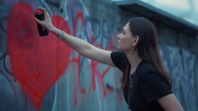 Girl drawing graffiti on wall. Focused woman painting heart with spray bottle