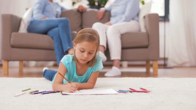 girl drawing with crayons in sketchbook at home - tappeto video stock e b–roll