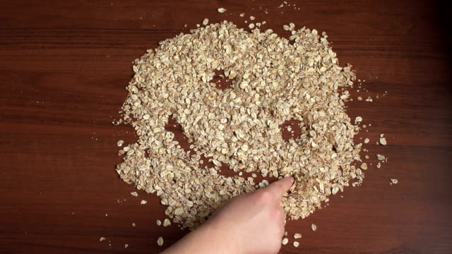 vídeos de stock e filmes b-roll de girl draws a smiley fase of oatmeal on the table. - oats