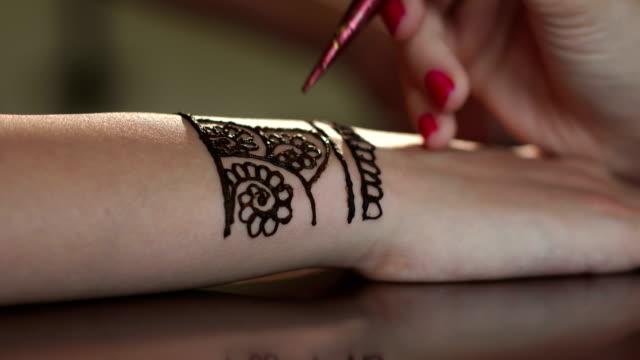 Girl draws mehndi on the hand. Close-up. 4K video