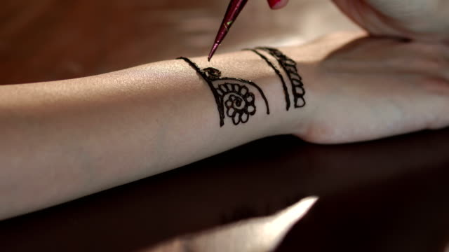 Girl draws mehndi on the hand. Close-up. video