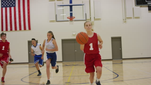 Girl dribbling basketball up court Young middle school girl dribbling a basketball up the court during a coed basketball game match sport stock videos & royalty-free footage