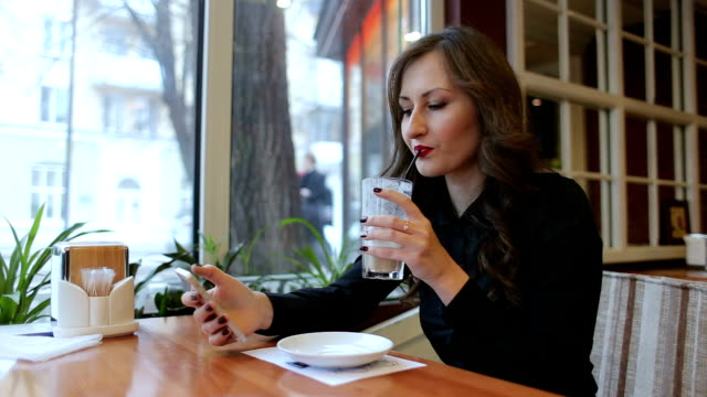 girl drinking cappuccino and looking at the phone. - rossetto rosso video stock e b–roll