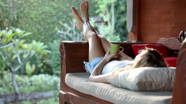 girl drinking coffee / tea and enjoying the sunrise / sunset in garden. - portico video stock e b–roll