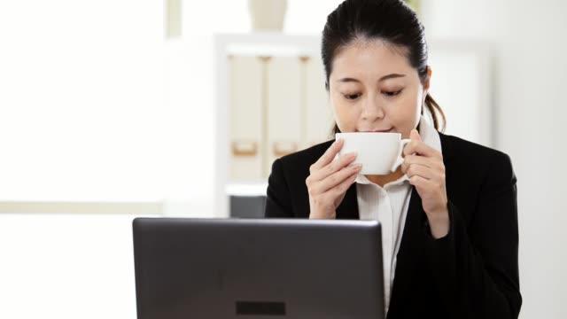 モバイル コンピューターでコーヒー作業を飲む女の子 - マグカップ点の映像素材/bロール