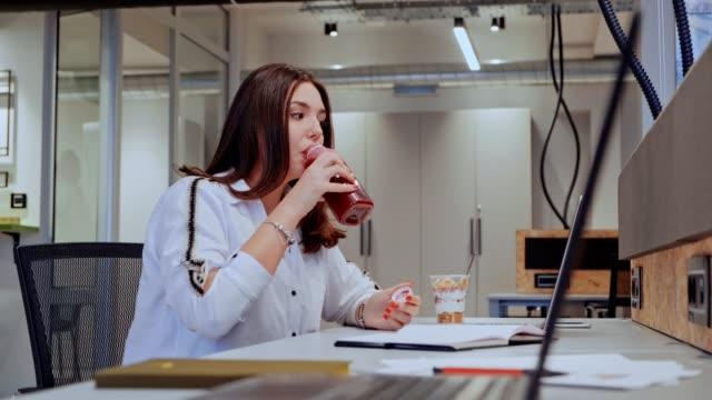 vídeos y material grabado en eventos de stock de chica bebiendo zumo y mirando la pantalla del ordenador - antioxidante