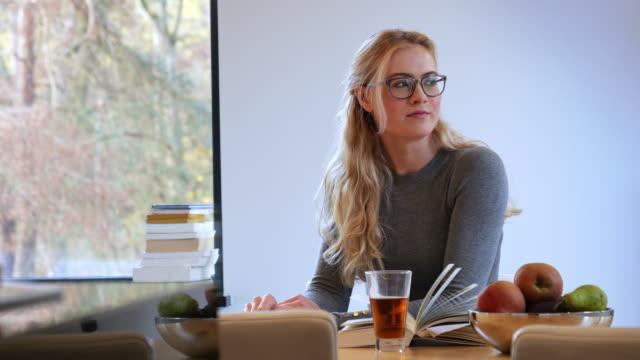 stockvideo's en b-roll-footage met meisje hete thee drinken en lezen van boek - woman home magazine