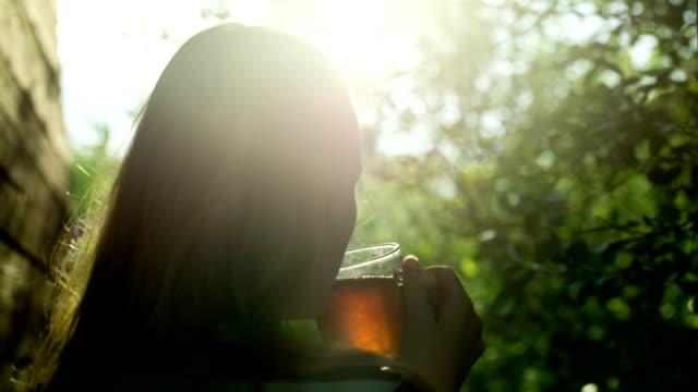 vídeos de stock, filmes e b-roll de menina, bebendo chá quente ao ar livre ao pôr-do-sol - tea drinks