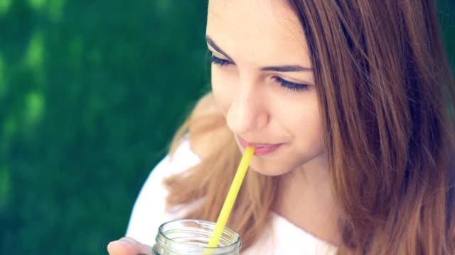Girl drinking iced tea with peach. video