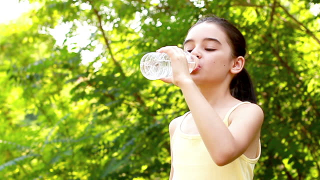 Girl drinking water out of a plastic bottle video