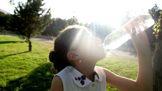 girl drinking water outdoors - acqua potabile video stock e b–roll