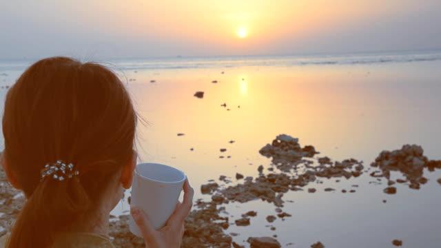 bir kız deniz arka plan üzerinde kahve içecekler - i̇nsan sırtı stok videoları ve detay görüntü çekimi