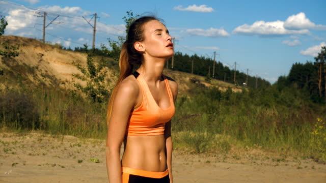 女の子は屋外スポーツ ・ トレーニング後水を飲む - 女性選手点の映像素材/bロール