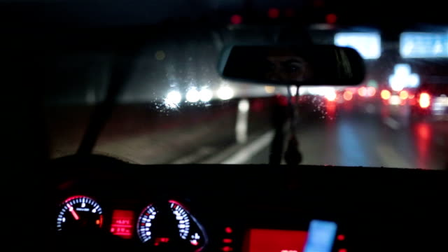 Girl driving a car on a rainy night Female driving in Austria on the highway while raining. rear view mirror stock videos & royalty-free footage
