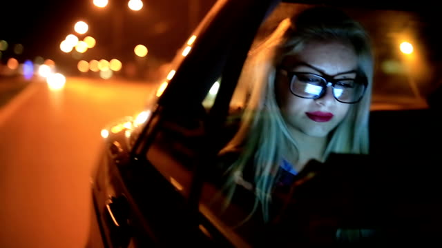 Girl driving at night in the car and working on digital tablet video