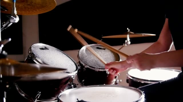 Girl drummer takes turns beats on each drum