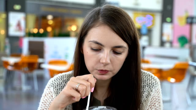 Girl eating brownie with ice cream in a cafe
