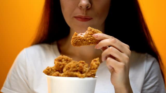 dziewczyna jedząca skrzydełka kurczaka, wysokokaloryczne jedzenie i zagrożenia dla zdrowia, cholesterol - węglowodan jedzenie filmów i materiałów b-roll