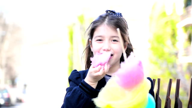 Girl eating cotton candy Beautiful,little girl is outdoors. She is eating cotton candy. cotton candy stock videos & royalty-free footage