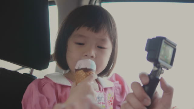 車のアイス クリーム コーンを食べる女子高生 ビデオ