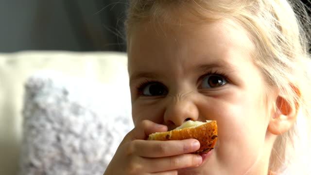 tjej äter smörgås och titta på tv i vardagsrummet - cheese sandwich bildbanksvideor och videomaterial från bakom kulisserna