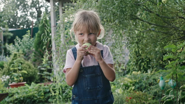 Girl Eating Sour Apple in Green Garden video