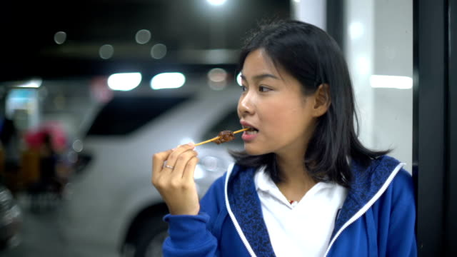 Girl eats chicken barbeque on wooden skewer in night street video