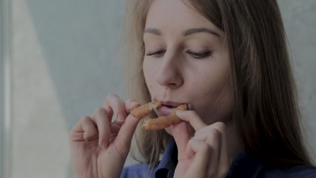 Girl eats onion rings and smiles in a fast food restaurant Girl eats onion rings and smiles in a fast food restaurant onion ring stock videos & royalty-free footage