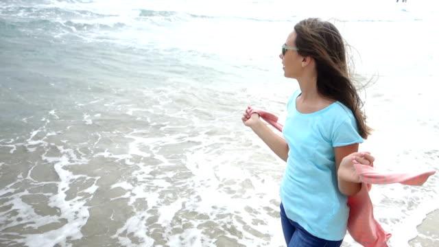 tjej som njuter av en promenad vid havet - endast en tonårsflicka bildbanksvideor och videomaterial från bakom kulisserna