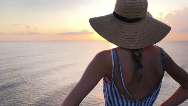 stockvideo's en b-roll-footage met meisje genieten op de oceaan/zee uitzicht bij zonsondergang tijd. - handen op de heupen