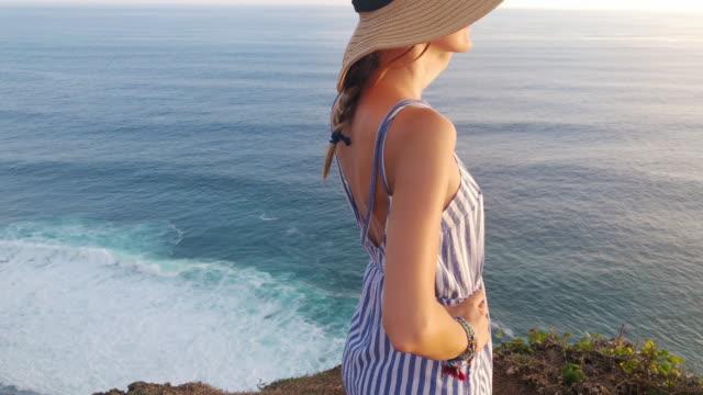 stockvideo's en b-roll-footage met meisje genieten van het uitzicht op de oceaan/zee vanaf een hoge klif. - handen op de heupen