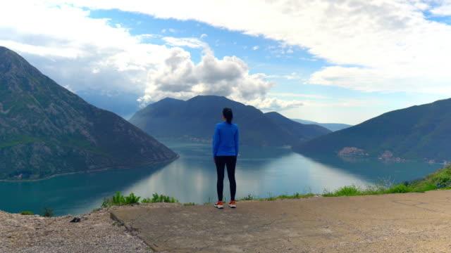 flicka njuter av vacker natur. berg och sjö på bakgrund - jogging hill bildbanksvideor och videomaterial från bakom kulisserna