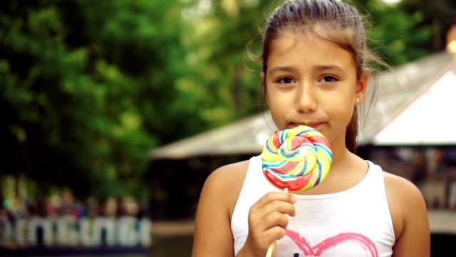 女孩享受大棒棒糖 - 波板糖 個影片檔及 b 捲影像