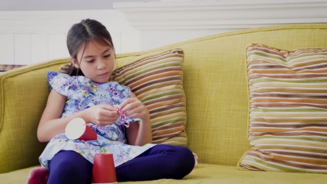 Girl enjoying playing tin can phone n the living room at home, 9 years old
