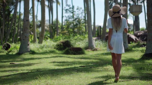 vídeos y material grabado en eventos de stock de chica disfrutando del paseo entre palmeras tropicales - disquete