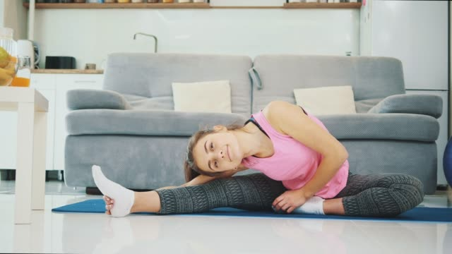A girl enjoys fitness at home while smiling.