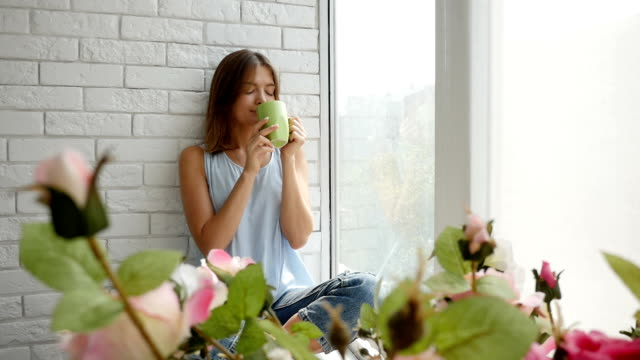 Girl enjoys the moment of relaxing and drinking a cup of aroma coffee on the window-sill video