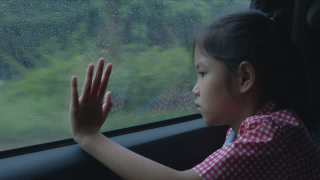 Girl enjoys to touch on car glass and looking outside in the rainy day
