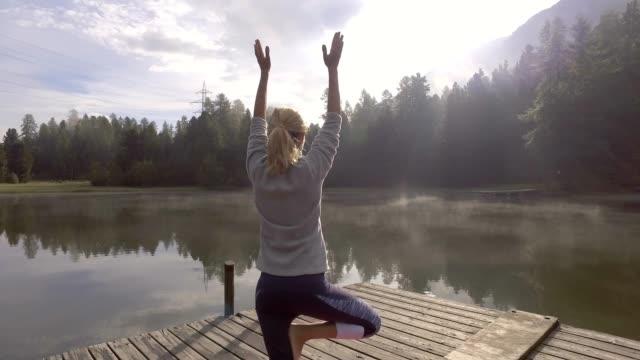 Girl exercising yoga in nature, Switzerland