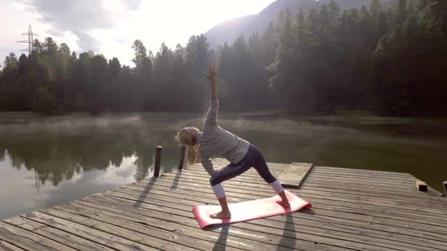 Girl exercising yoga in nature, Switzerland video