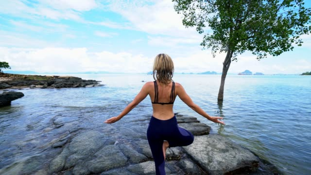 Girl exercising yoga in nature video