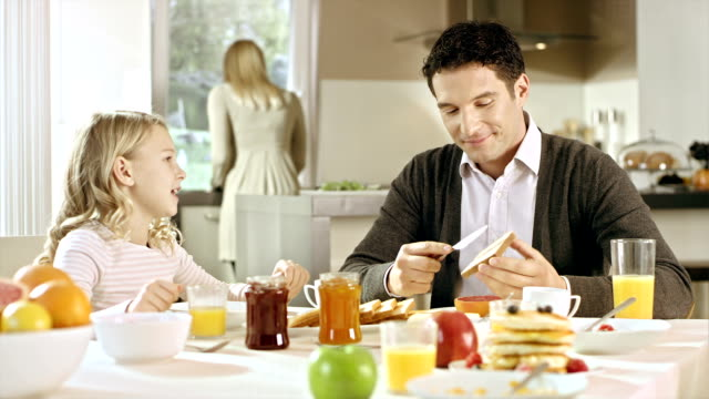 Girl explaining something to her father at breakfast video