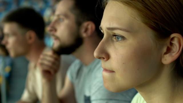 vídeos de stock e filmes b-roll de girl fan with friends watching sport game or races at stadium, worried, anxious - adeptos