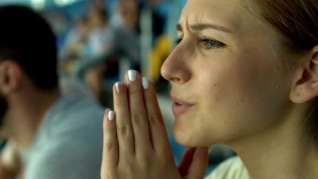 Girl fan worries about sport game or races, praying superstitious, face closeup Girl fan worries about sport game or races, praying superstitious, face closeup match sport stock videos & royalty-free footage